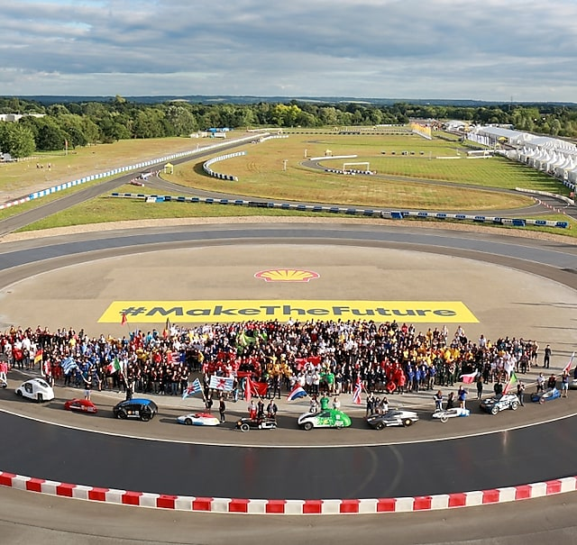 Shell Eco-marathon teams and cars stand together on track