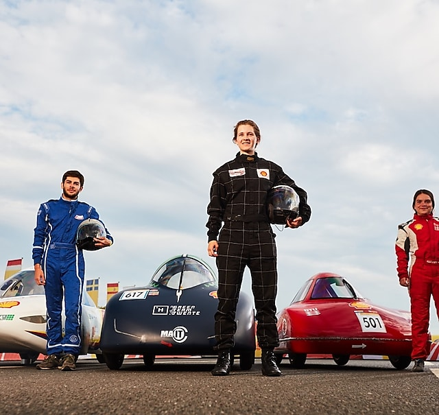 Three drivers stand in front of their vehicles